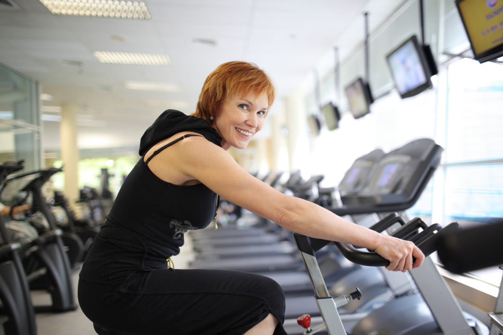 Happy mature woman exercising on a stationary bike in gym