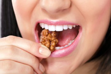 Close up of a woman's mouth eating a nut