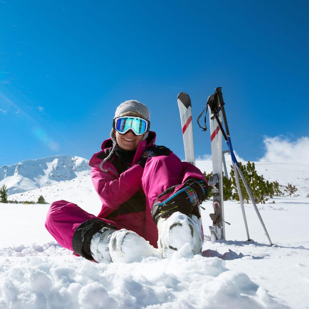 Female skier resting on the ski slope, bright blue sky behind