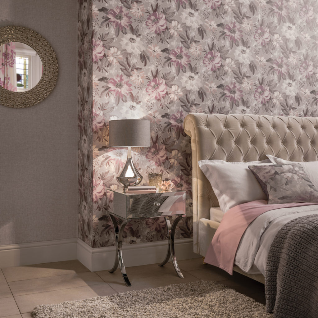 Comfortable bedroom in soft pink, lilac and taupe, bed with studded velour headboard and subtle floral wallpaper