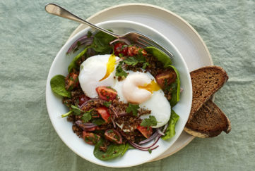 Poached eggs on top of bowl of salad