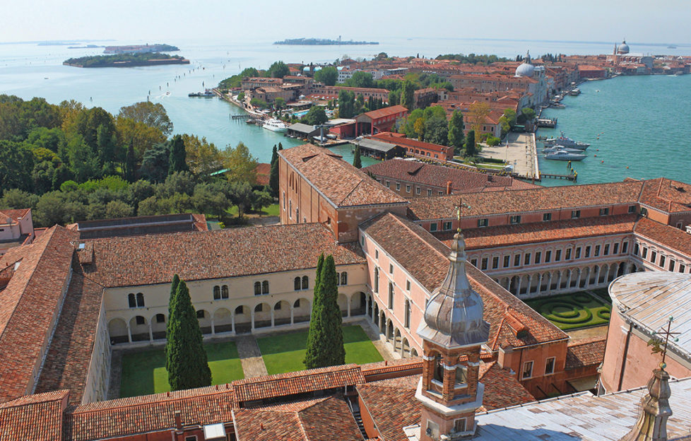 Venice: Pink brick quadrangles with manicured lawns, seen from tower, also turquoise water and an island with similar buildings in the middle distance
