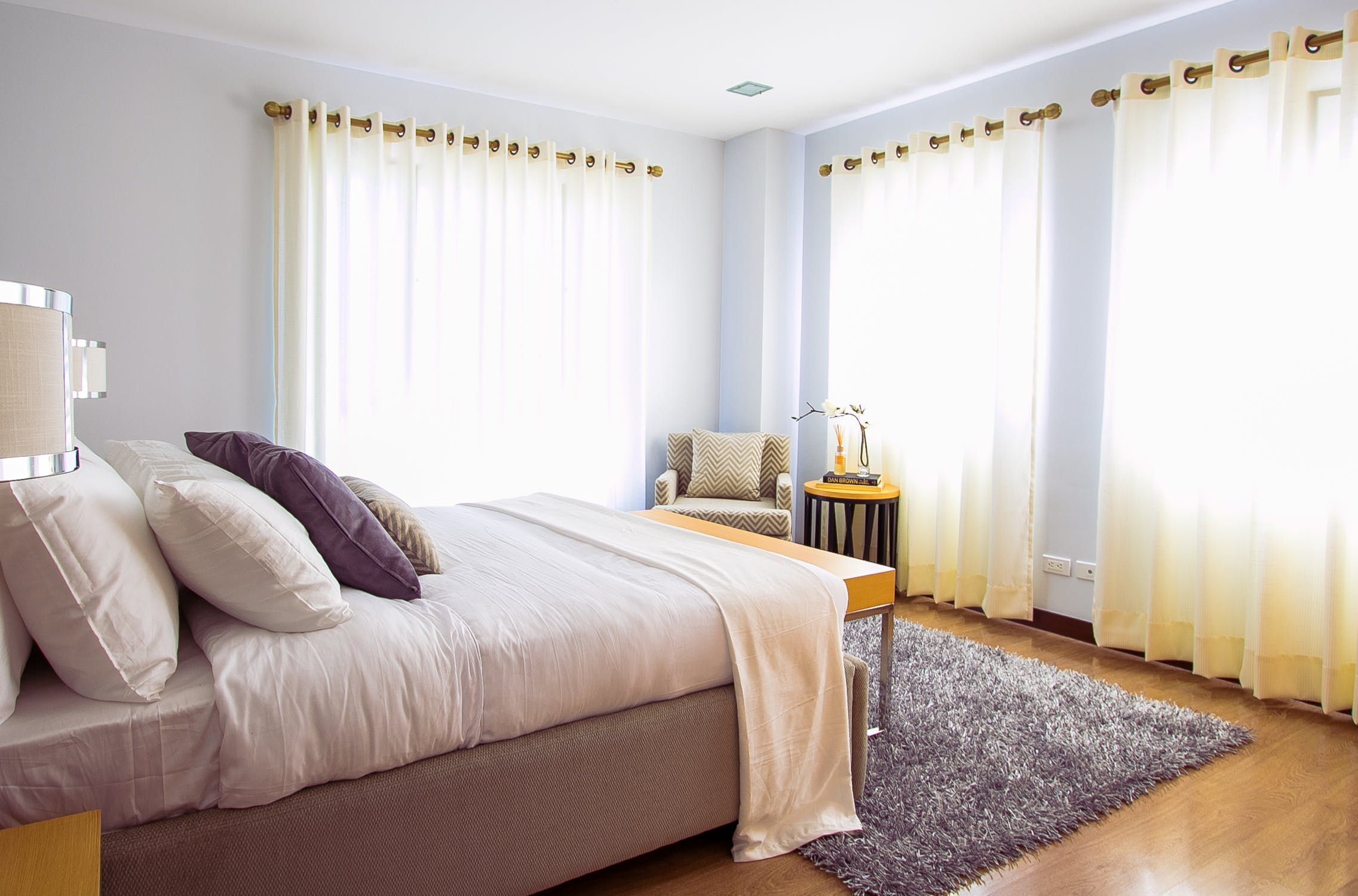 Modern bedroom, gauzy white eyelet curtains on poles allowing sunlight to stream in