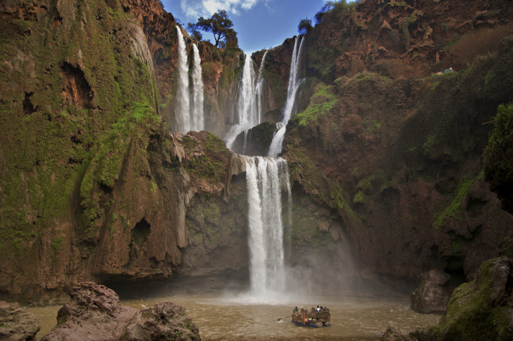Tourist raft in water dwarfed by 2 tier red rock formation and impressive waterfall