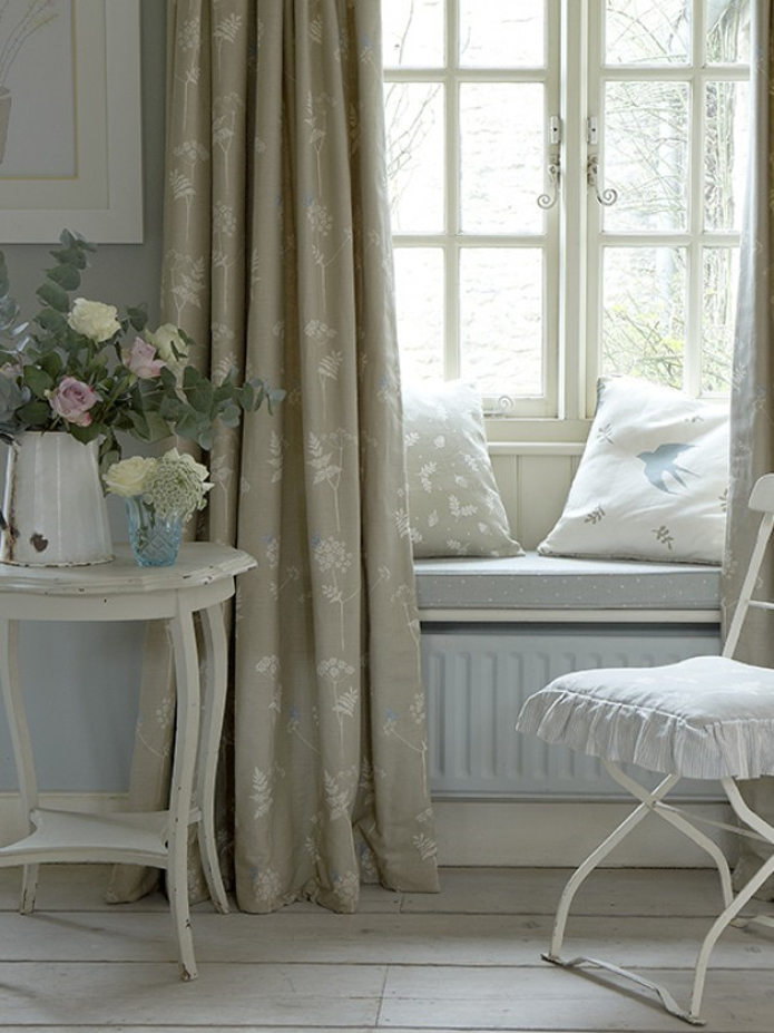 Subtle elegant taupe curtains with cream flower stems, window seat behind