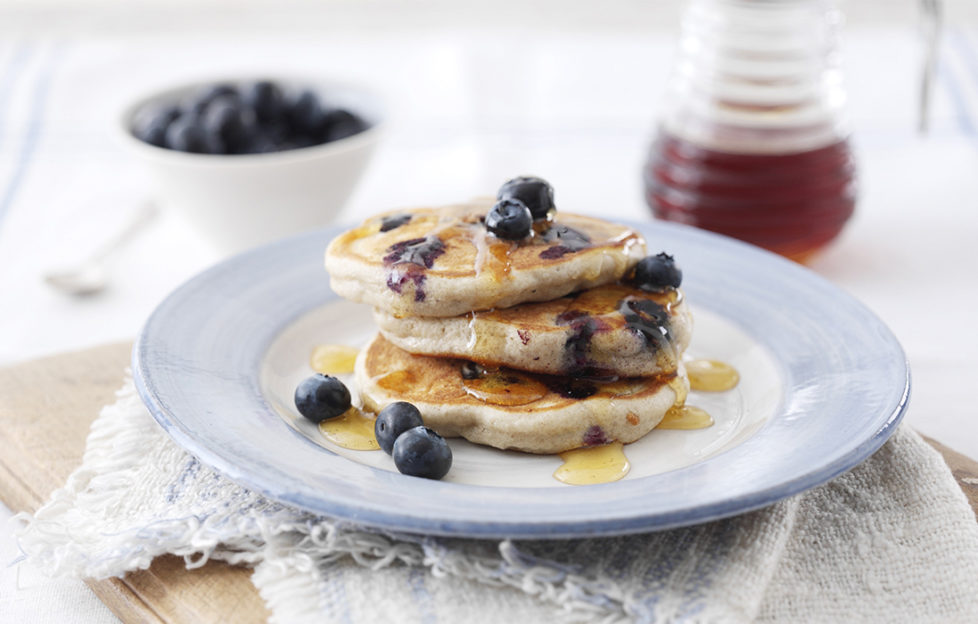 Stack of 3 small thick golden pancakes served with blueberries and syrup
