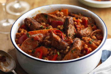 Round white casserole dish filled with mixture of sausage, barley, tomatoes and peppers