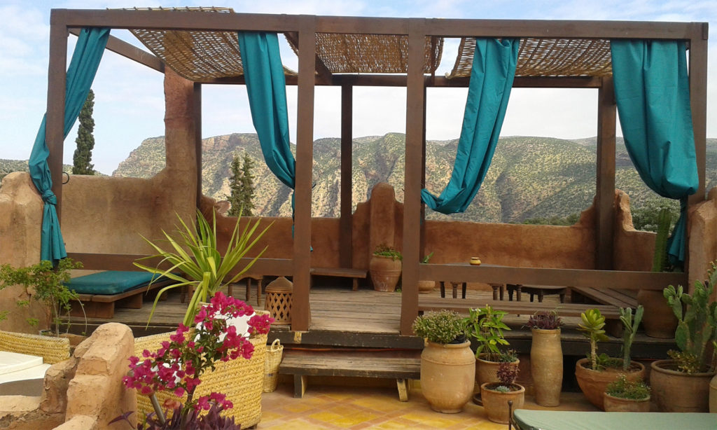 Raised seating area with stone walls, woven roof panels, green curtains and view over rocky hillside