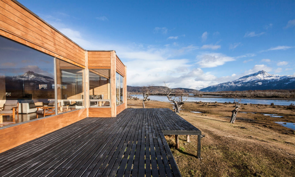 Hotel with open wooden terrace on stilts, overlooking river and hills beyond