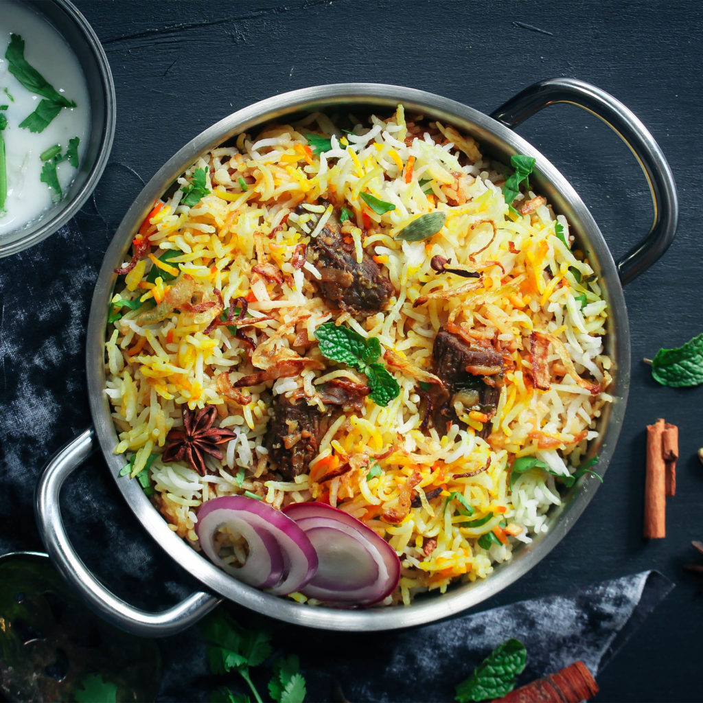 Big pot of colourful rice biryani with fresh coriander, star anise and slices of raw red onion