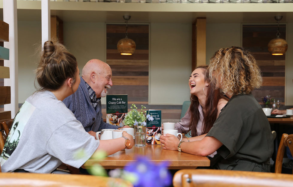 Three young people and an older man laughing together at a cafe table