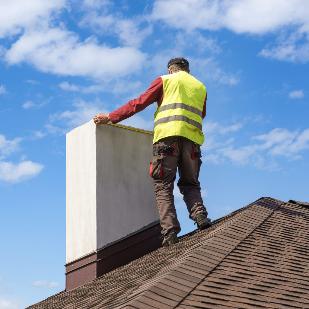 Professional workman standing on roof top and measuring chimney of new house