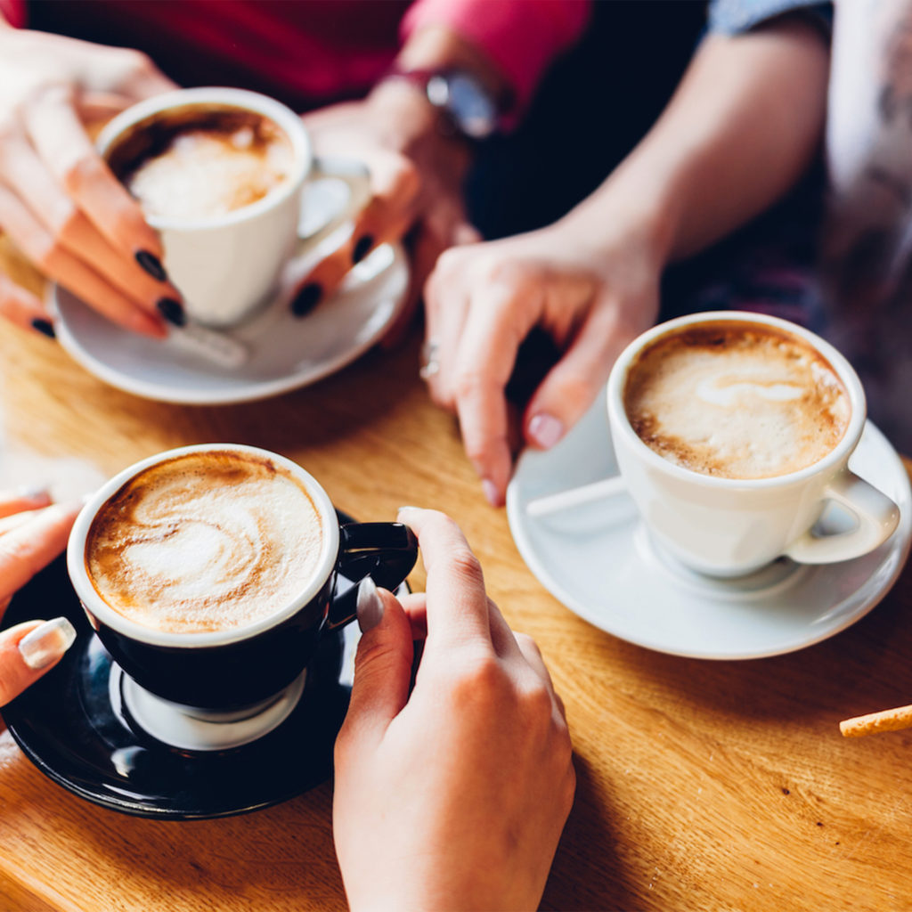 Three people sitting at a table with cups of coffee