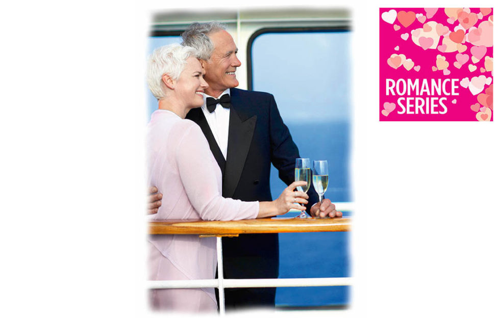 Mature couple in evening dress with glasses of sparkling wine lean on rail of cruise ship deck