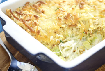 Golden cheese topped bake, spoonful removed showing leek and chicken