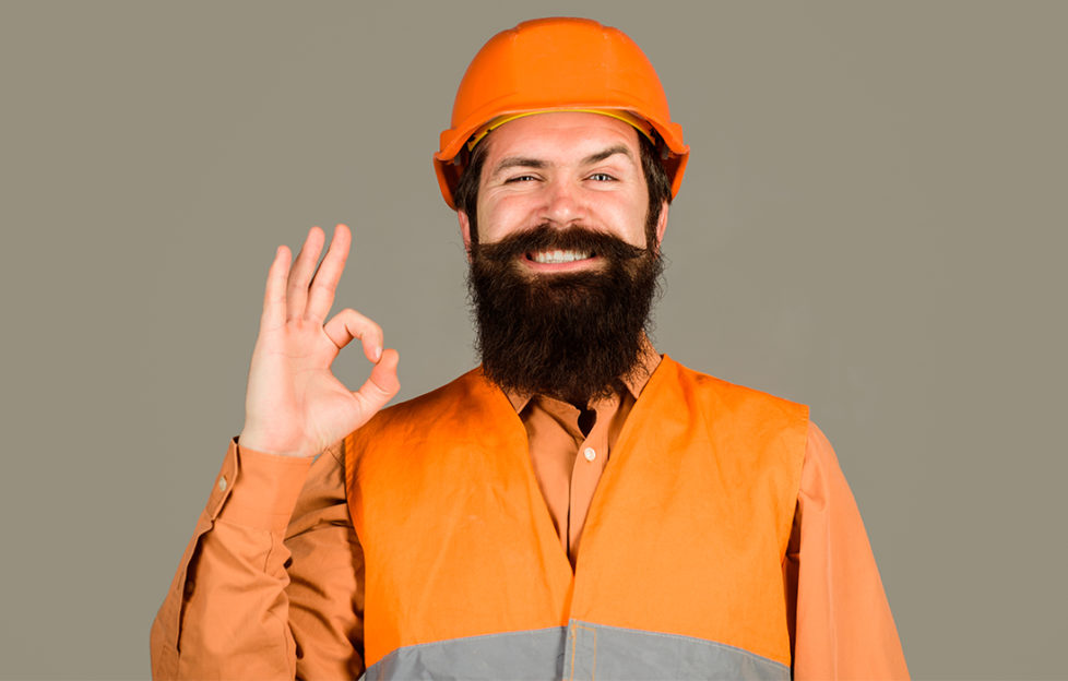 Tradesperson in orange hard hat and hi-vis vest giving OK symbol with finger and thumb