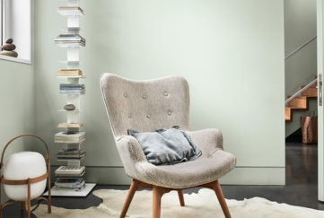 Comfy curved modern chair in front of pale green wall and tall, narrow modern shelf