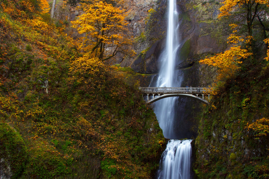 Narrow silvery waterfall plummets hundreds of feet passing metal bridge that crosses in front of it halfway up. Picturesque autumn trees