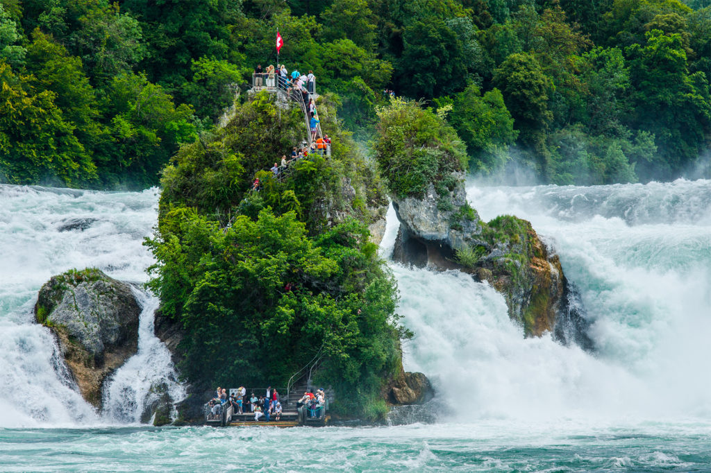 Tall, narrow rocky island amid river and waterfalls. People are climbing steps to the top.