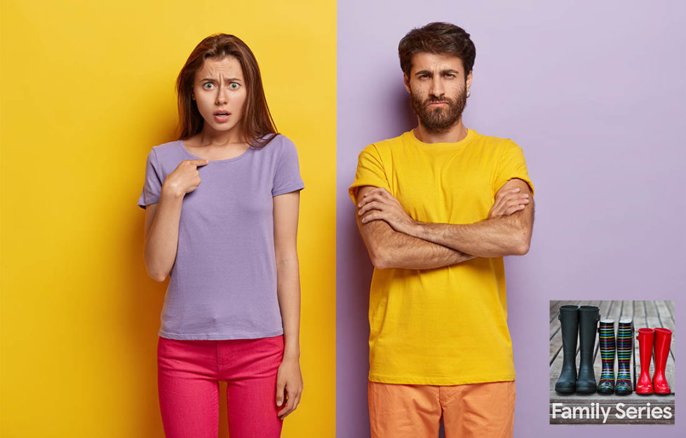 "Girl in purple t shirt against yellow wall, man in yellow t shirt against purple wall. He looks defensive, she is asking, ""what, me?"""