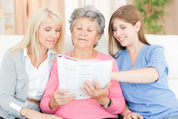 Three women looking at magazine Pic: Istockphoto