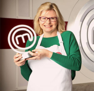 Smiling blonde woman with glasses in white apron holding Masterchef trophy