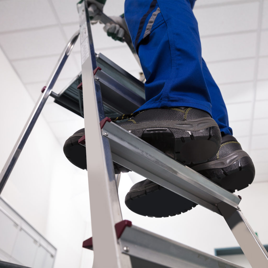 Close-up Of Man Standing On Steel Ladder