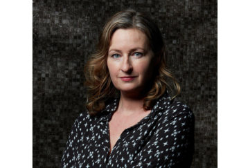 Portrait shot of author Louise Candlish against dark background