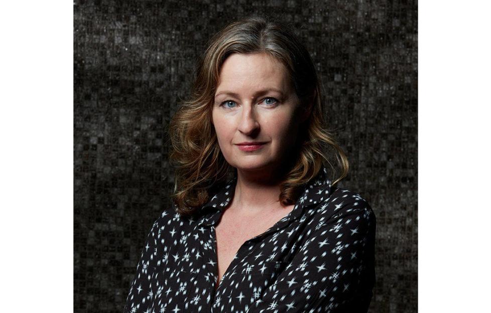 Portrait shot of author Louise Candlish against dark background