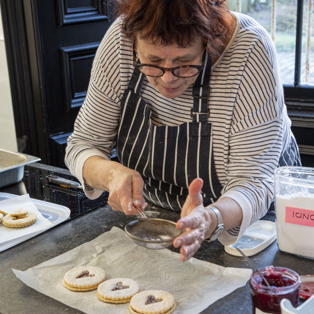 Home economist Maxine sprinkles icing sugar over Jammie Dodger style biscuits