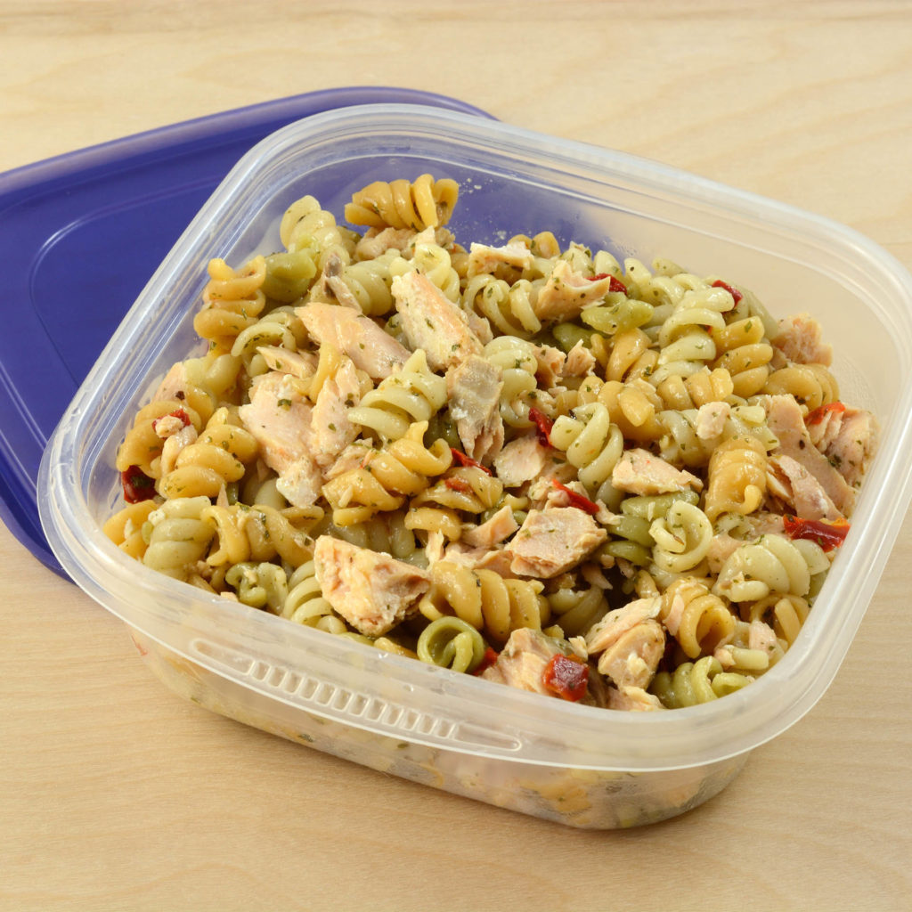 Pasta salad in Tupperware style square tub, blue lid tucked underneath