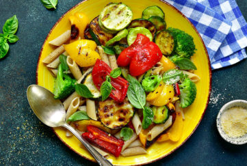 Plate of pasta bake and roasted or grilled pepper and courgette, garnished with fresh basil leaves