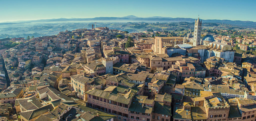 Panoramic bird eye view of Siena, Italy, taken from Torre del Mangia (highest tower in Siena). The dominant building on the right is Siena Cathderal.; Shutterstock