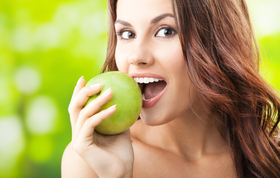 Woman biting into green apple outdoors