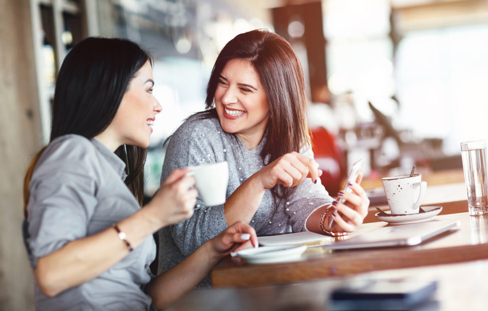 2 smiling women having chat in cafe