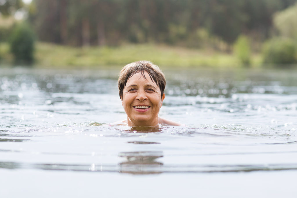 Healthy senior woman swimming in the lake or river. Happy elderly lady enjoying active summer vacation.