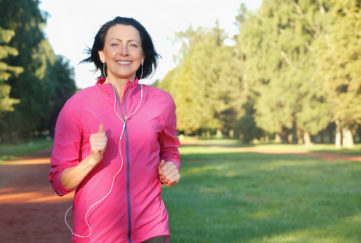 Portrait of elderly woman running with headphones in the park in early morning. Attractive looking mature woman keeping fit and healthy