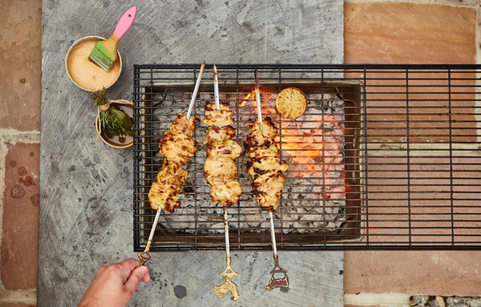 Three skewers of chicken chunks in creamy sauce being grilled over a barbecue