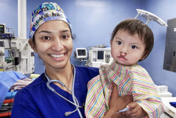 Smiling nurse with toddler who has just had a cleft lip operation, red scars above lip