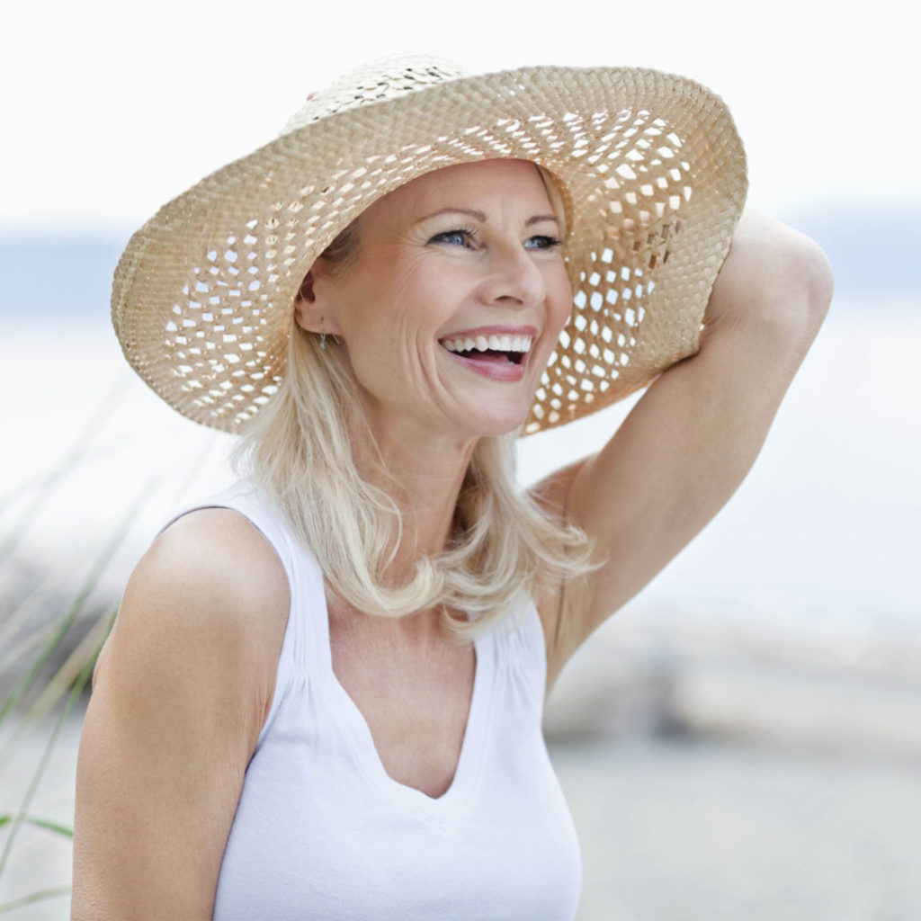 Laughing mature woman at the beach, holding a straw sunhat on her head so it doesn't blow away