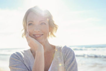 Smiling woman on beach, wearing sleeved top, sun behind