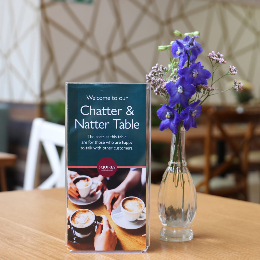 Table in cafe with small vase of flowers and Chatter And Natter sign: This table is for people who are happy to talk to other customers.
