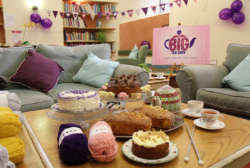 Cosy living room with bunting and balloons, plus cakes and balls of yarn on coffee table