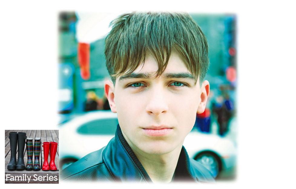 Dark haired teenage boy looks pleadingly into camera