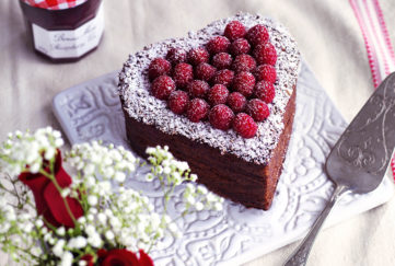 Heart shaped chocolate Valentine cake topped with fresh raspberries, on table with vase of red roses and gypsophila and jar of Bonne Maman conserve