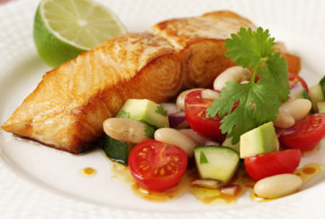 Fillet of salmon on plate with cucumber chunks, cherry tomato halves, beans and avocado pieces, half a lime on the side