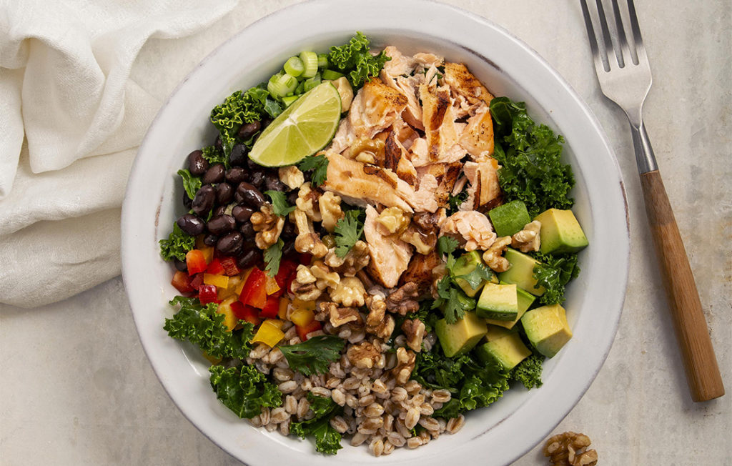 Bowl of salad with flaked salmon, crushed walnuts, cubed pepper and avocado, kale and lime wedge