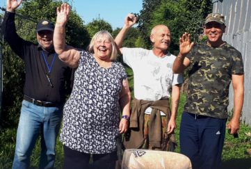 Four people at allotments with wheelbarrow, smiling and waving
