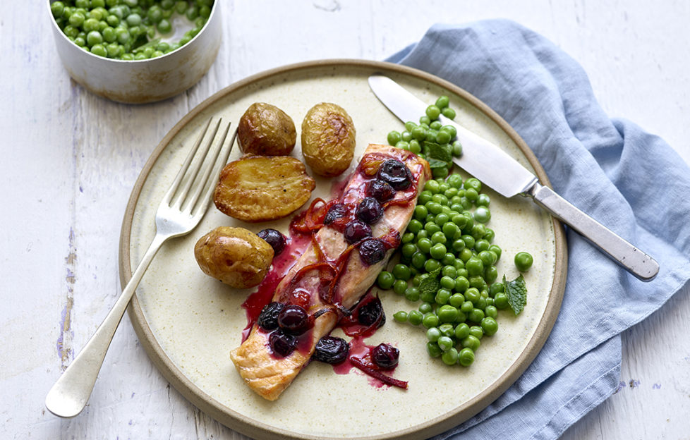 Plate with salmon fillet topped with cooked blueberries and drizzle of deep red sauce, roast potatoes and peas on the side