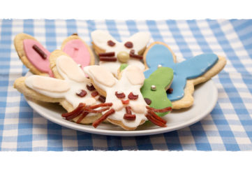 Plate of bunny head shape biscuits with different coloured icing and whiskers etc made out of dried fruit pieces
